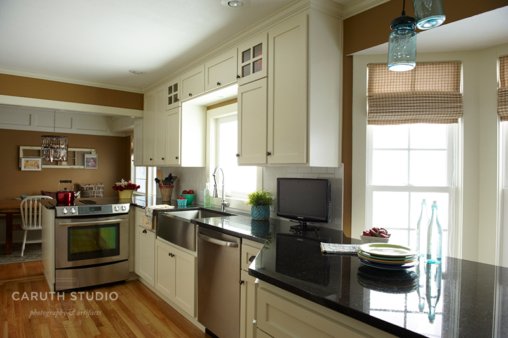 New kitchen cabinets in white with antiqued brass half moon handles and black countertop
