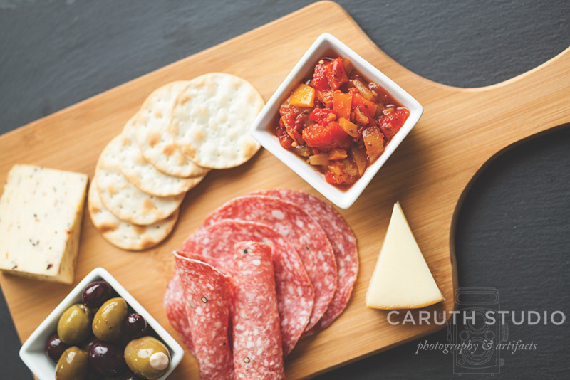 Antipasto with crackers, cheese and olives on wooden cheese board