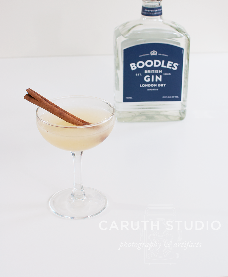 Modern English with cinnamon stick in coup glass with gin