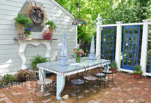Repurposed patio with door, mantel, table and chairs