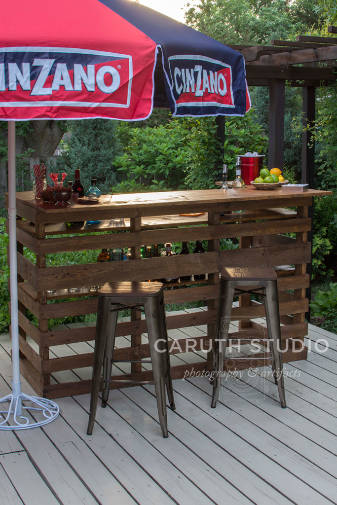 pallet bar with umbrella and bar chairs ready for a party