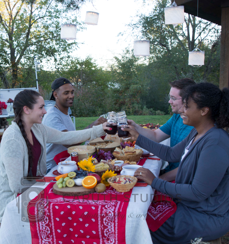 four friends toasting an outdoor chili party