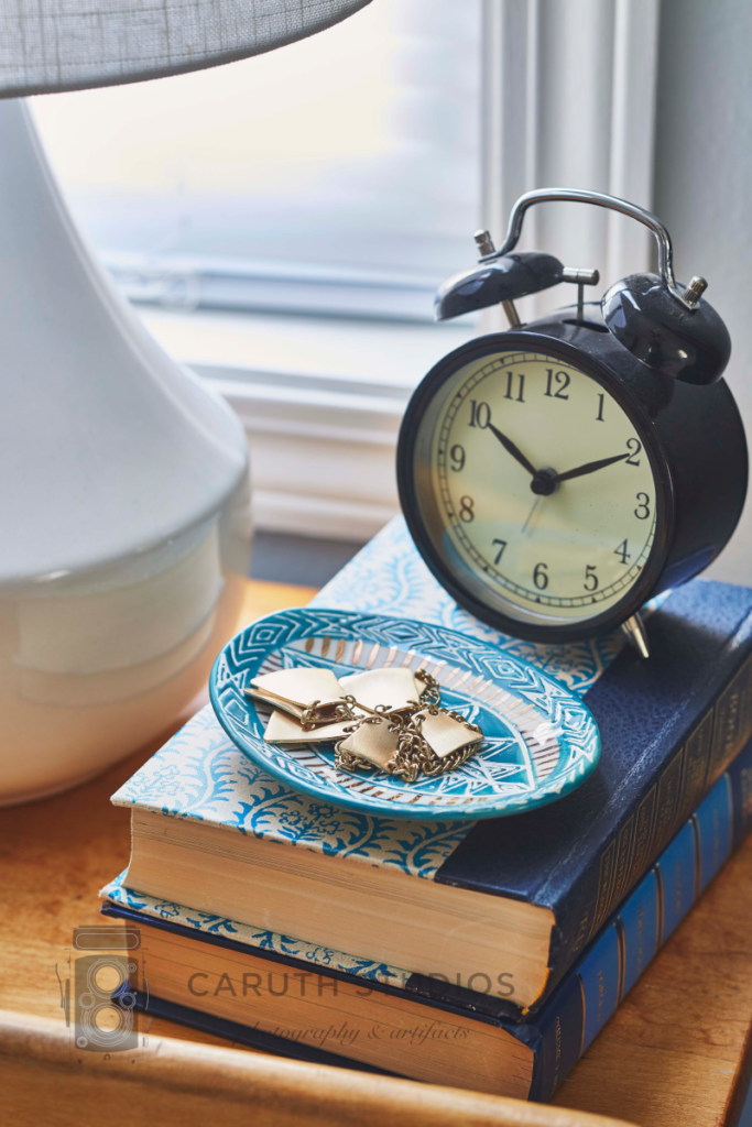 Stack of books, jewelry bowl and clock on nightstand