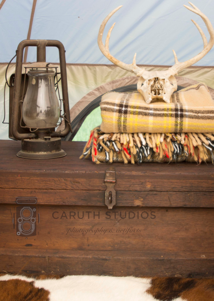 deer skull and plaid blankets and rustic lantern on top of wooden trunk