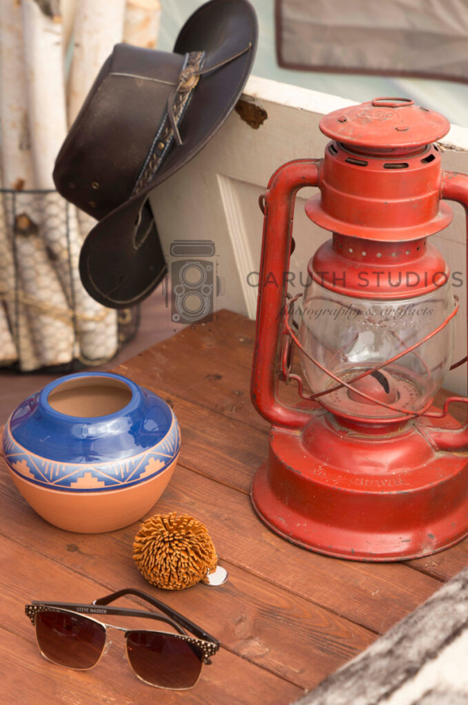 bedsite table with rustic lantern, native american pottery and cowboy hat
