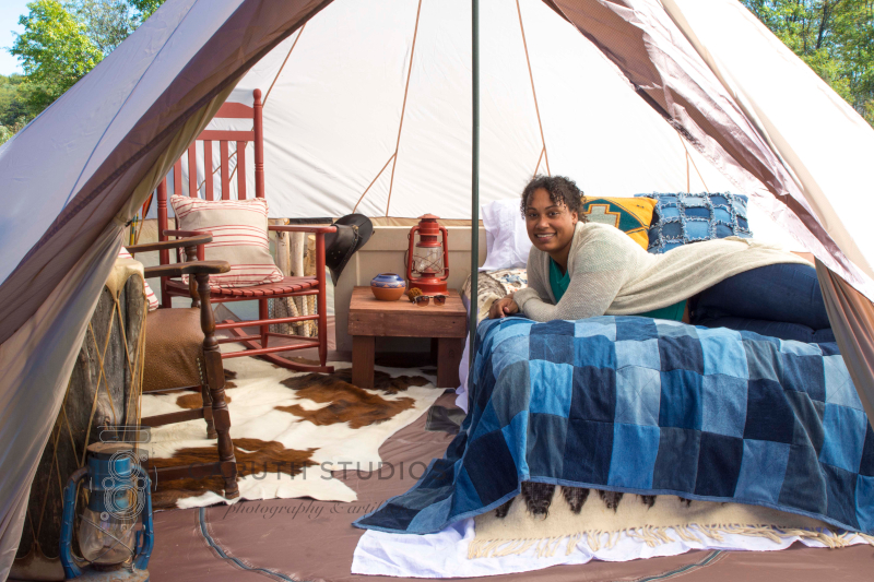 woman laying on bed in southwest tipi style tent