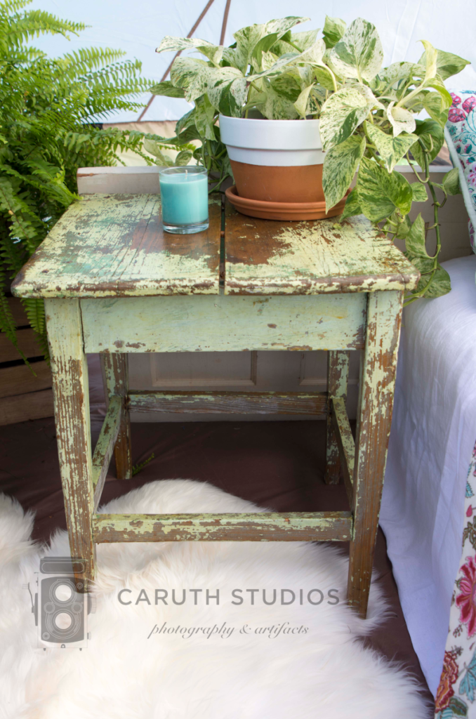 distressed wooden nightstand with potted plant